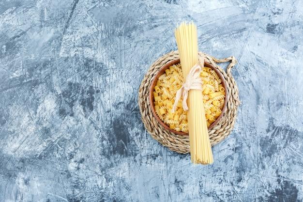 Vista superior de pasta variada en un recipiente sobre fondo gris de yeso y mantel de mimbre. horizontal