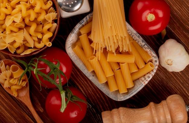 Vista superior de pasta ziti en un tazón con espagueti y otros tipos en un tazón y una cuchara de sal, tomate, ajo en la superficie de madera