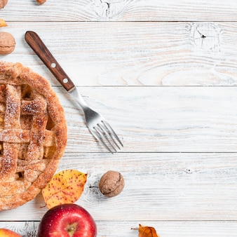 Vista superior de pastel apetitoso con tenedor y manzana