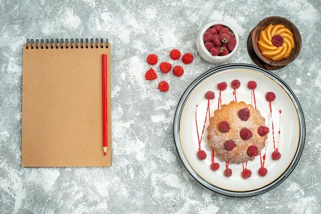 Vista superior de pastel de bayas en placa ovalada blanca galleta en tazón de madera frambuesas en tazón de fuente lápiz rojo portátil sobre superficie gris
