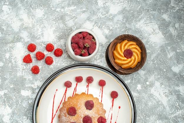 Vista superior de pastel de bayas en placa ovalada blanca galleta en tazón de madera frambuesas en tazón sobre superficie gris