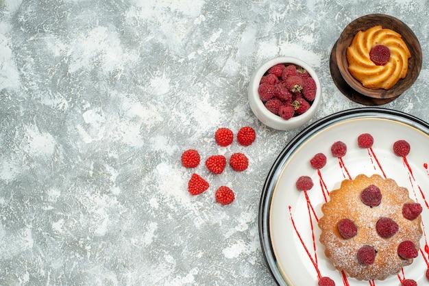 Vista superior de pastel de bayas en tazón de galleta de placa ovalada blanca con frambuesas en espacio libre de superficie gris