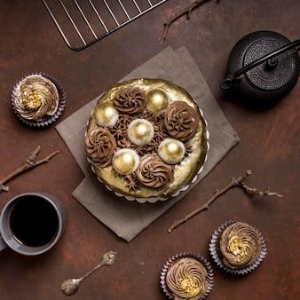 Vista superior de pastel con café y cupcakes