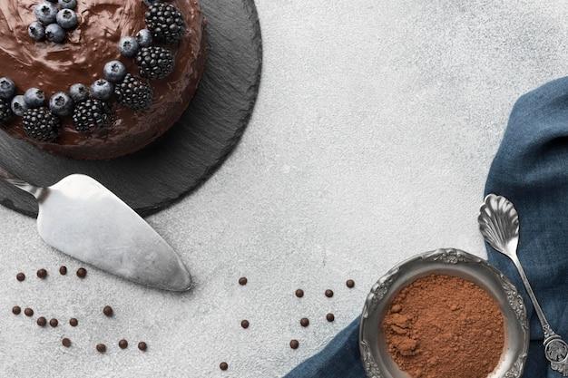 Vista superior del pastel de chocolate con arándanos y espátula