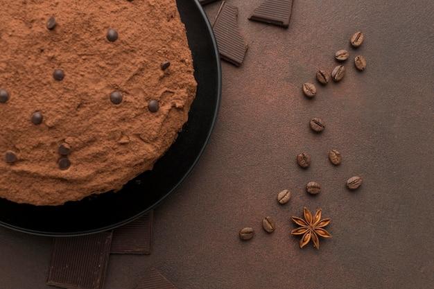 Vista superior del pastel de chocolate con cacao en polvo y granos de café.