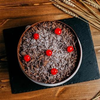 Una vista superior pastel de chocolate decorado con cerezas redondas deliciosas dentro de pastel marrón