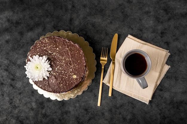 Vista superior de pastel con cubiertos y taza de café