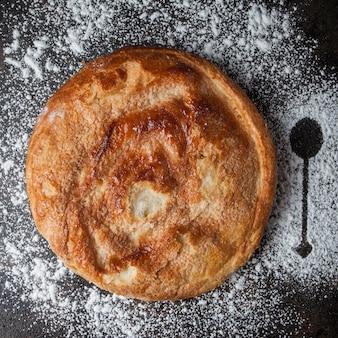 Vista superior de pastel con harina y cuchara silueta