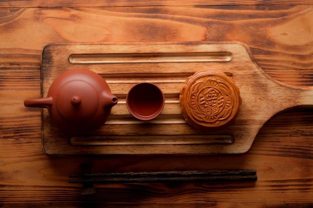 Vista superior del pastel de luna tradicional y juego de té en tablero de madera. el carácter chino en el pastel de luna representa