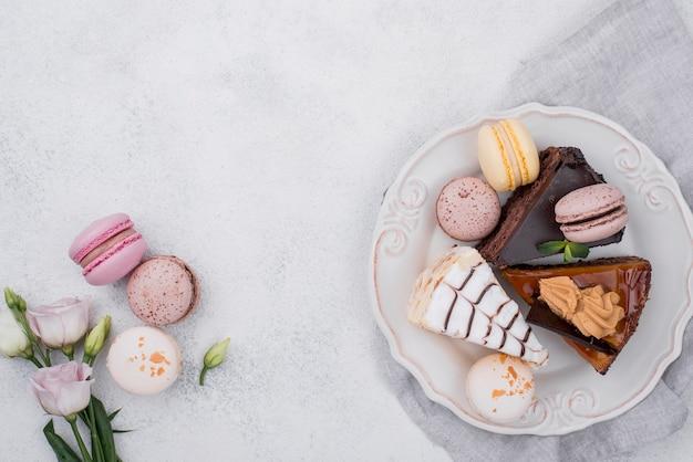 Vista superior del pastel en un plato con macarons y rosa