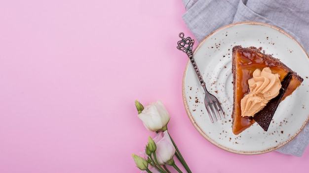 Vista superior del pastel en un plato con rosas y espacio de copia