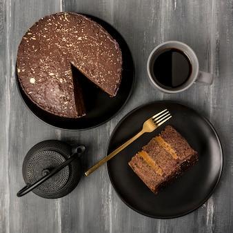Vista superior de pastel en plato con tenedor y café
