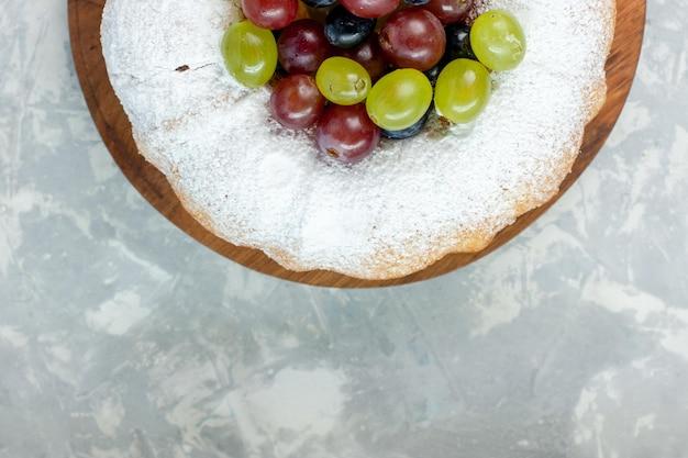 Vista superior pastel en polvo delicioso pastel horneado con uvas frescas sobre superficie blanca