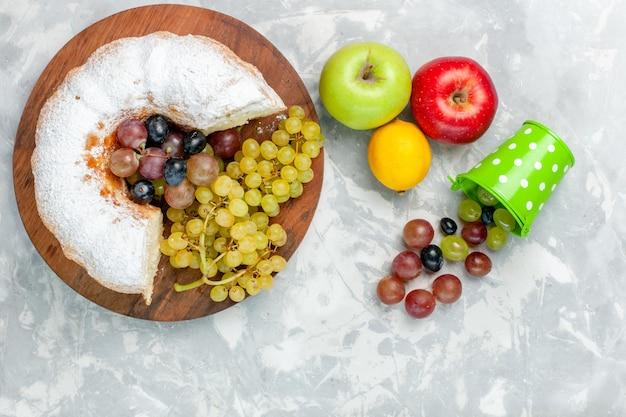 Vista superior de pastel en polvo con uvas frescas y manzanas en el escritorio blanco