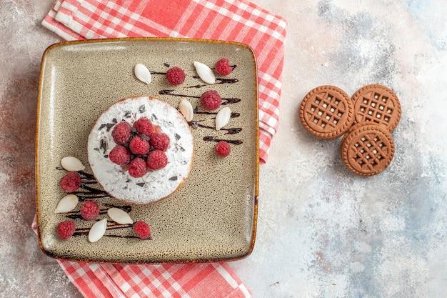 Vista superior del pastel recién horneado con frambuesas y galletas en el cuadro blanco