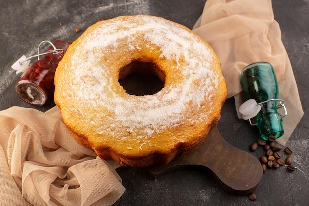 Una vista superior de pastel redondo horneado con azúcar en polvo y semillas de café en el escritorio de madera