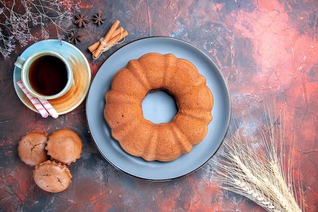 Vista superior de un pastel, una taza de té, plato azul de pastelitos, magdalenas, canela, anís estrellado, espigas de trigo