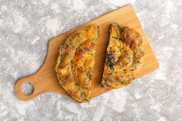 Vista superior de pastelería con carne deliciosa masa en rodajas sobre superficie de luz blanca