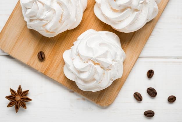 Vista superior pasteles de crema con granos de café