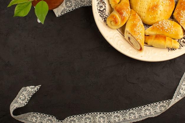 Vista superior pasteles y cruasanes delicioso plato interior delicioso sobre el fondo oscuro