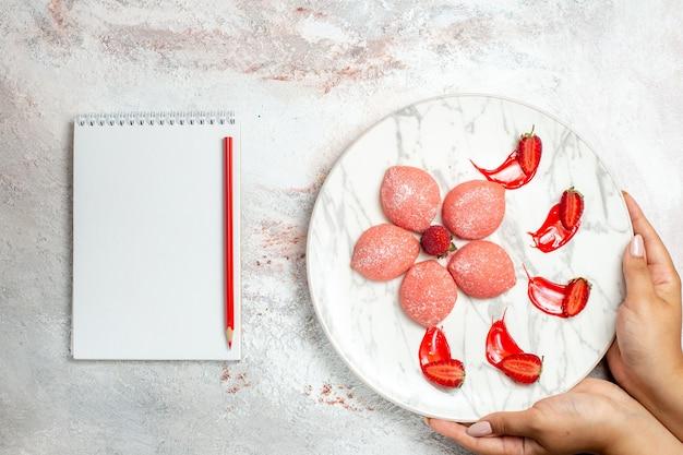 Vista superior pasteles de fresa rosa pequeños dulces deliciosos en el escritorio blanco galleta azúcar té dulce pastel de galleta
