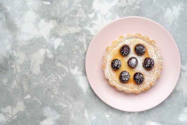 Vista superior del pastelito con azúcar en polvo y frutas en la luz, pastel de frutas y bayas hornear pastel