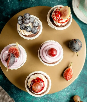 Vista superior de pastelitos de chocolate decorados con crema de vainilla, higos, uvas y arándanos