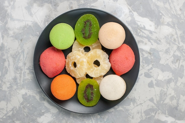 Vista superior de pastelitos de colores con anillos de piña secos sobre la superficie blanca clara