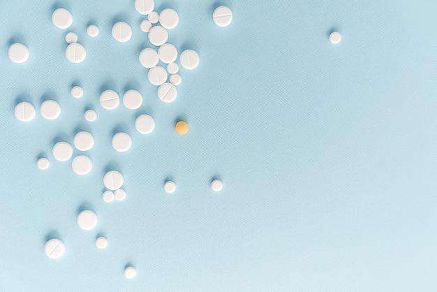 Vista superior de pastillas blancas con tableta amarilla