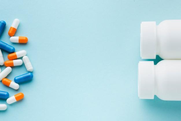 Vista superior de pastillas de colores y botellas de plástico copia espacio