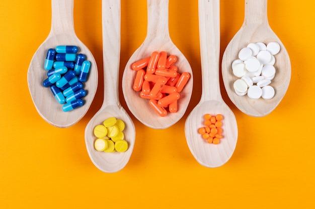 Vista superior de pastillas de colores en cucharas de madera sobre fondo naranja. horizontal