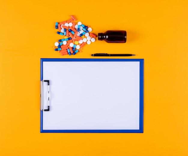 Vista superior de pastillas con soporte de papel y bolígrafo
