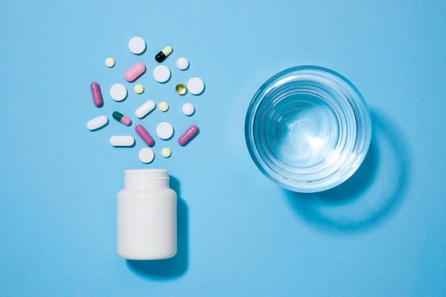 Vista superior de pastillas con vaso de agua