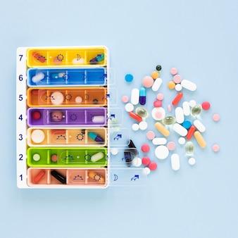 Vista superior de pastilleros de medicina sobre la mesa
