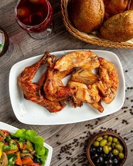 Vista superior de patas de pollo y alitas kebab dispuestas en un plato con una copa de vino en la mesa de madera