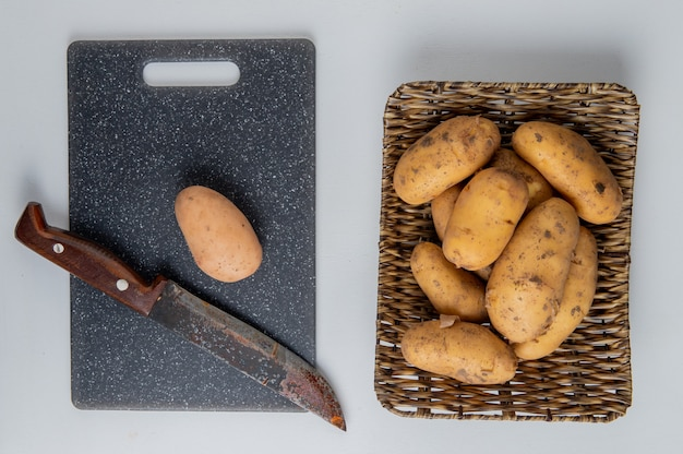 Vista superior de la patata y el cuchillo en la tabla de cortar con otros en el plato de la cesta sobre la superficie blanca