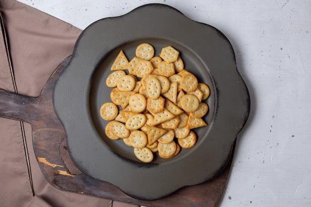 Vista superior de patatas fritas saladas dentro de un plato oscuro sobre el fondo gris, comida para el desayuno de galletas