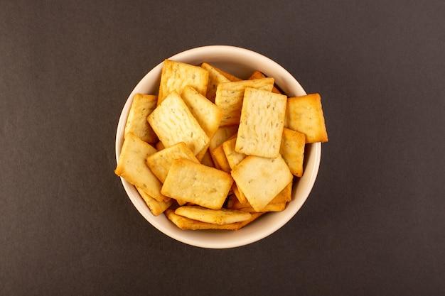 Una vista superior patatas fritas saladas sabrosas galletas de queso dentro de un plato blanco sobre el fondo oscuro bocadillo sal comida crujiente