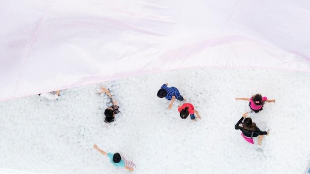 Vista superior del patio de recreo con globos con gente de la familia y niños jugando a la pelota blanca con el techo de tela textil en primer plano
