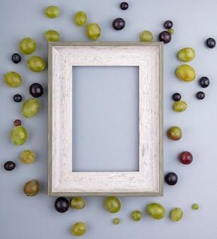 Vista superior del patrón de bayas de uva alrededor del marco sobre fondo gris con espacio de copia