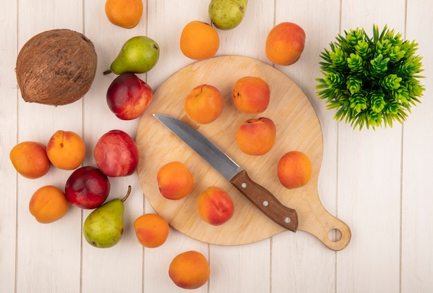 Vista superior del patrón de frutas como albaricoques con cuchillo en la tabla de cortar y patrón de peras melocotones de coco con flor sobre fondo de madera