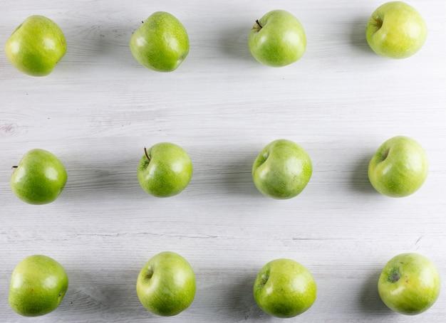 Vista superior del patrón de manzanas verdes en blanco horizontal de madera