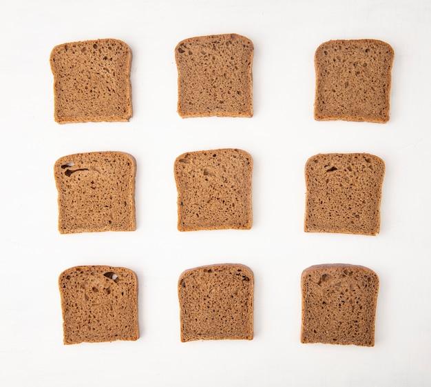 Vista superior del patrón de rebanadas de pan de centeno sobre fondo blanco.
