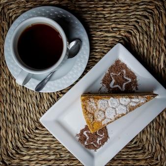 Vista superior del pedazo de pastel con una taza de té y una cuchara y un plato blanco en servilletas