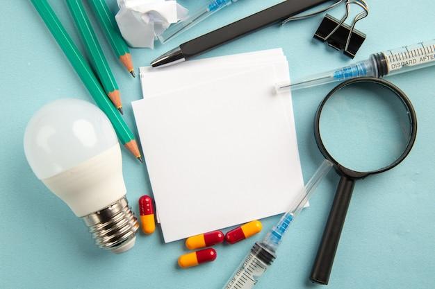 Vista superior pegatinas blancas con lápices, inyecciones y píldoras sobre fondo azul laboratorio ciencia pandemia hospital virus píldora covid color salud