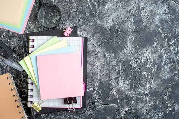 Vista superior de pegatinas de colores con cuaderno sobre fondo gris