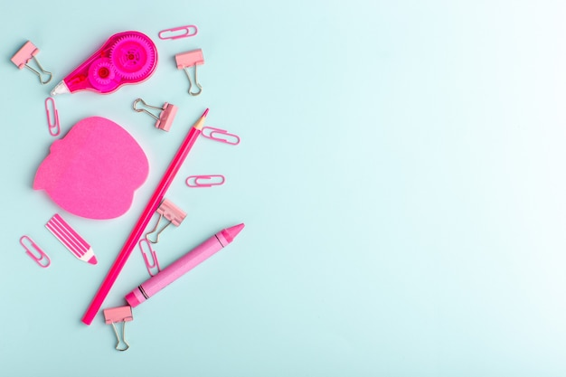 Vista superior de pegatinas rosas con pegatinas de metal y bolígrafo en la superficie azul