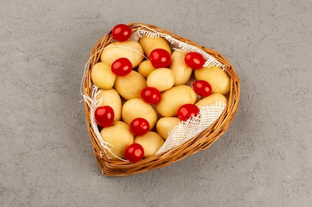 Vista superior pelado papas junto con tomates cherry rojos dentro de la canasta en el piso gris