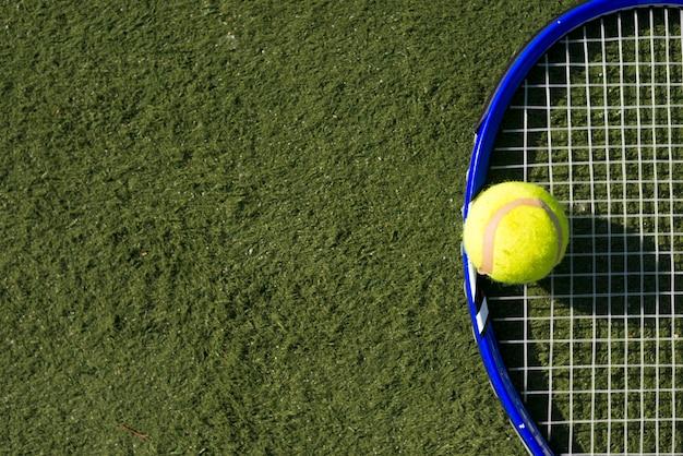 Vista superior de la pelota de tenis y raqueta con copia espacio.