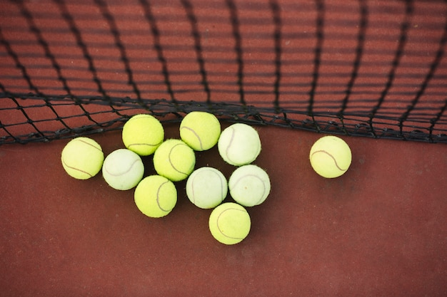 Vista superior pelotas de tenis al lado de la red en el campo